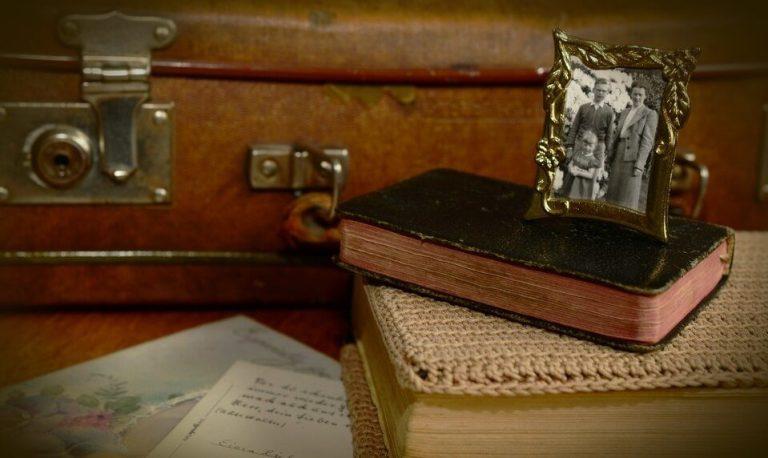 Es un veliz antiguo y enseguida esta un libro grueso una biblia con pasta negra que tiene una foto de una familia que se compone del padre madre y nina ademas estan unas cartas
