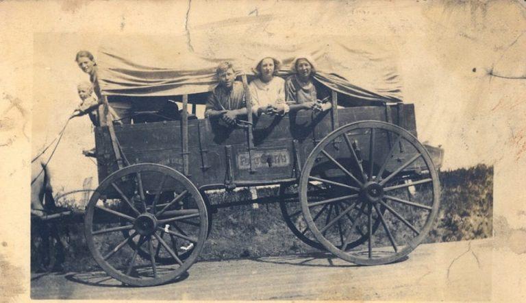 Es una carreta antigua que es jalada por caballos arriba esta una familia el padre y tres mujeres y un nino