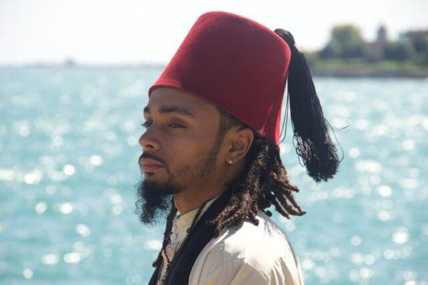 Es un hombre Moro con poca barba del Norte de Africa con un gorro rojo