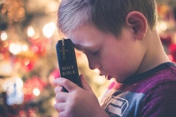 Es un nino orando con sus ojos cerrados y con su Biblia en sus manos