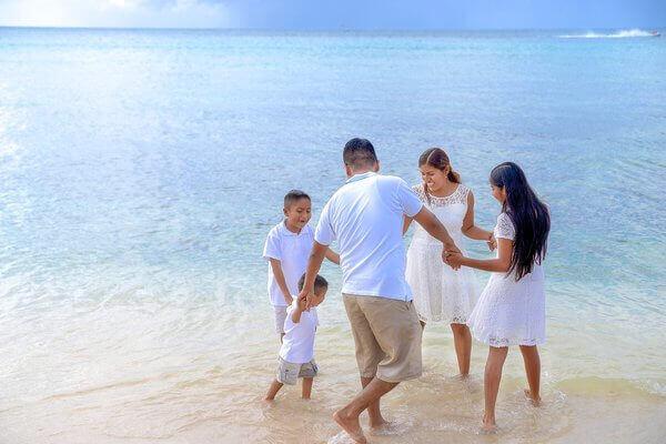 Es una familia a la orilla del mar jugando a la orilla de la playa