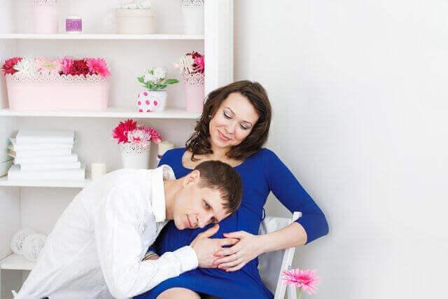 Es una pareja y ella esta embarazada y el tiene su cabeza en la barriga de su esposa para tratar de escuchar al bebe