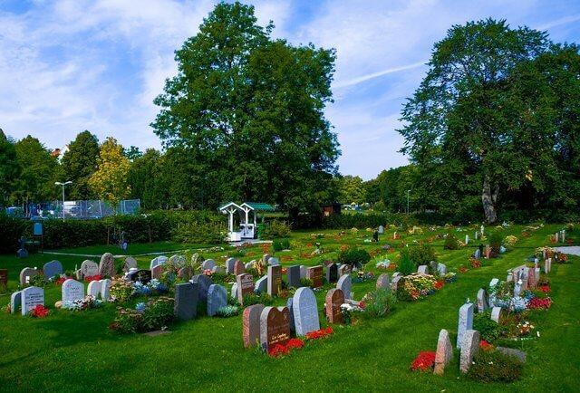 Es un cementerio con varias tumbas y la mayoria tienen flores