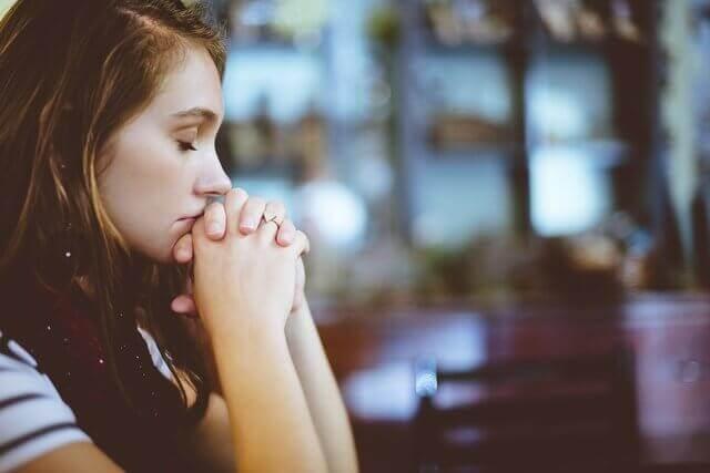 Una joven orando por los alimentos