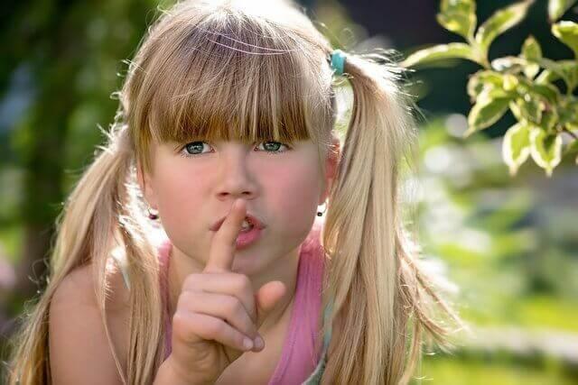 Es una nina que hace senas de que guardemos silencio