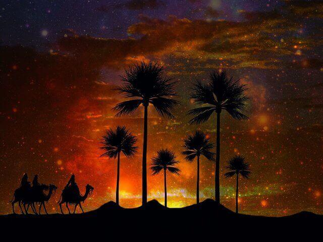 Esta anocheciendo y tres viajeros en camello estan llegando a un oasis