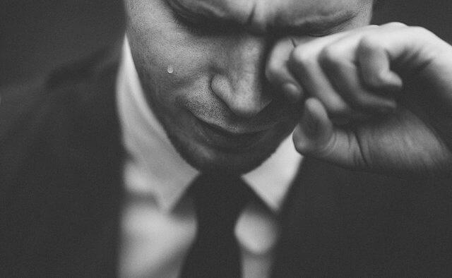 Es un hombre que esta agachado llorando
