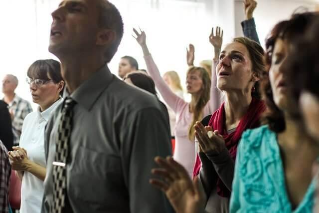 Es un grupo de personas orando a Dios