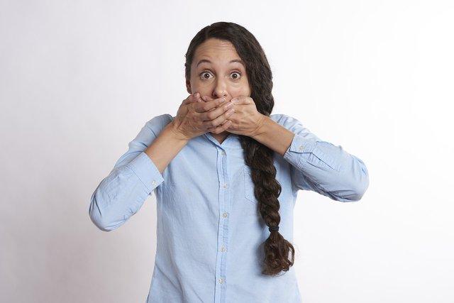 Es una mujer que se cubre la boca con sus dos manos