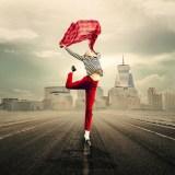 Es una joven en el centro de la autopista y brinca y tiene una panoleta roja en sus manos