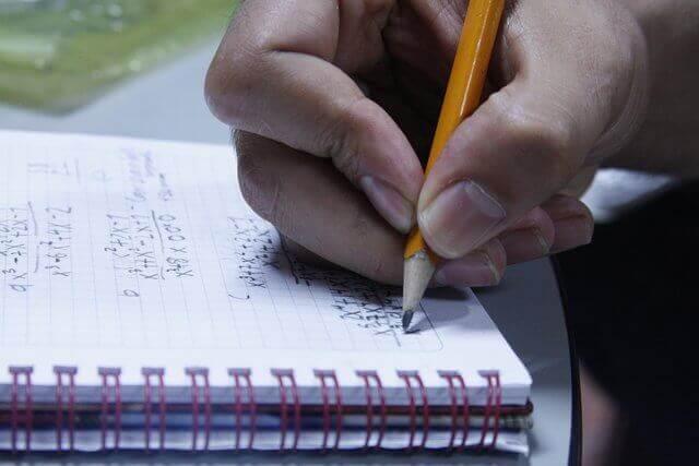 Es una mano que esta escribiendo en un cuaderno con un lapiz