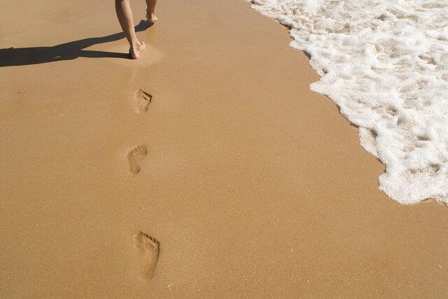 se ven solo los pies de una persona que va dejando huella en la arena de la orilla del mar