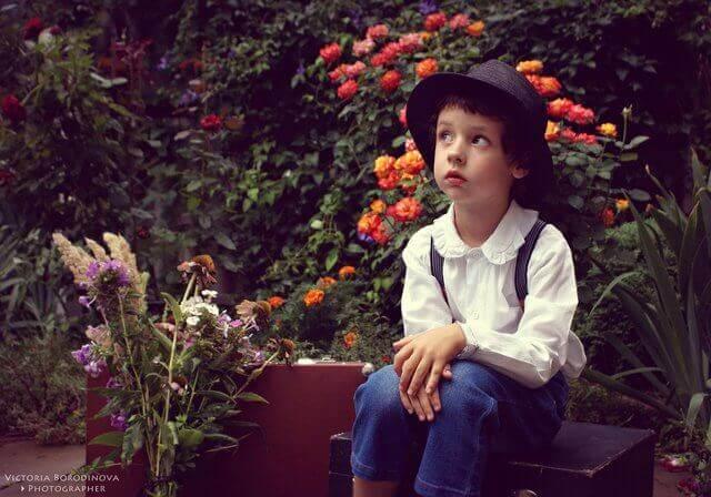 Es un nino pensativo sentado enmedio del jardin