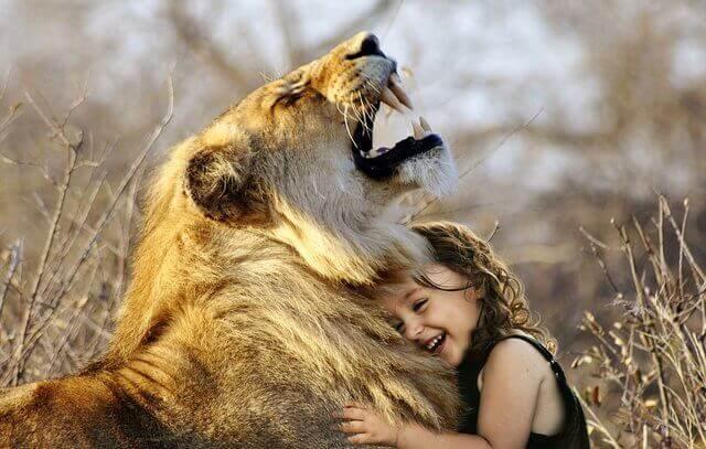 Es ubna nina riendo y recostada en el pecho de un leon