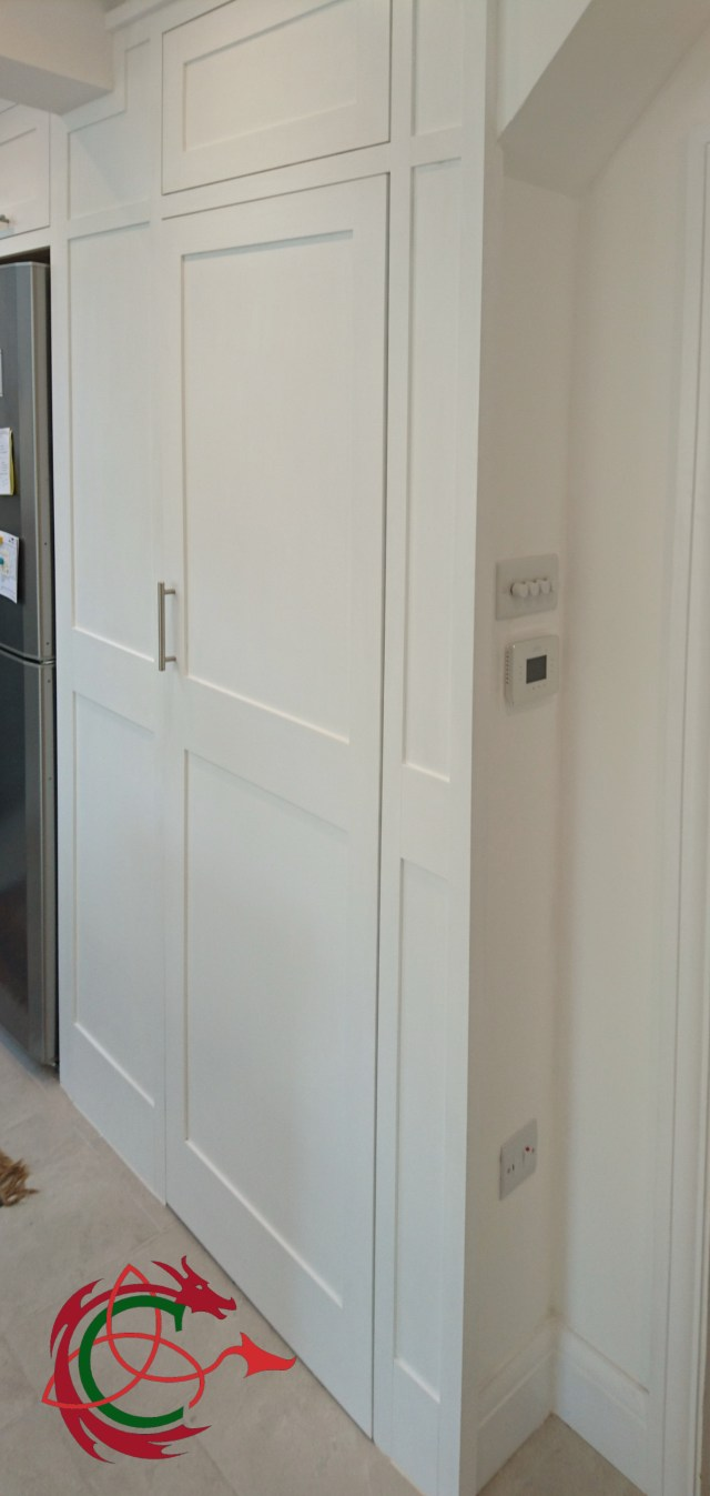 adapted stair cupboard in painted shaker kitchen, shown closed