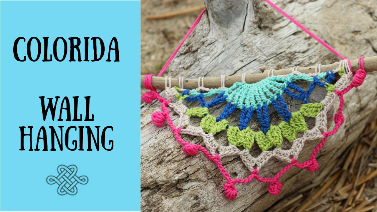 crocheted wall hanging made with many colors on driftwood