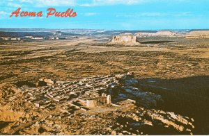 Aerial view of the Acoma Pueblo. The largest structure is San Esteban del Rey, which throws its shadow across the graveyard.