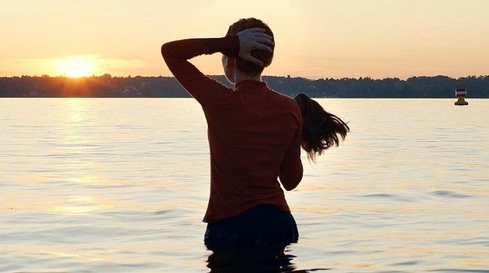 Esty (Shira Haas) entrando no lago sem a peruca que é obrigada a usar