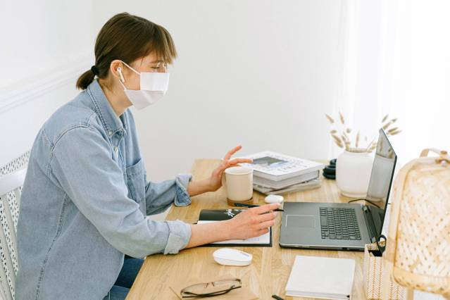woman with face mask looking at a laptop