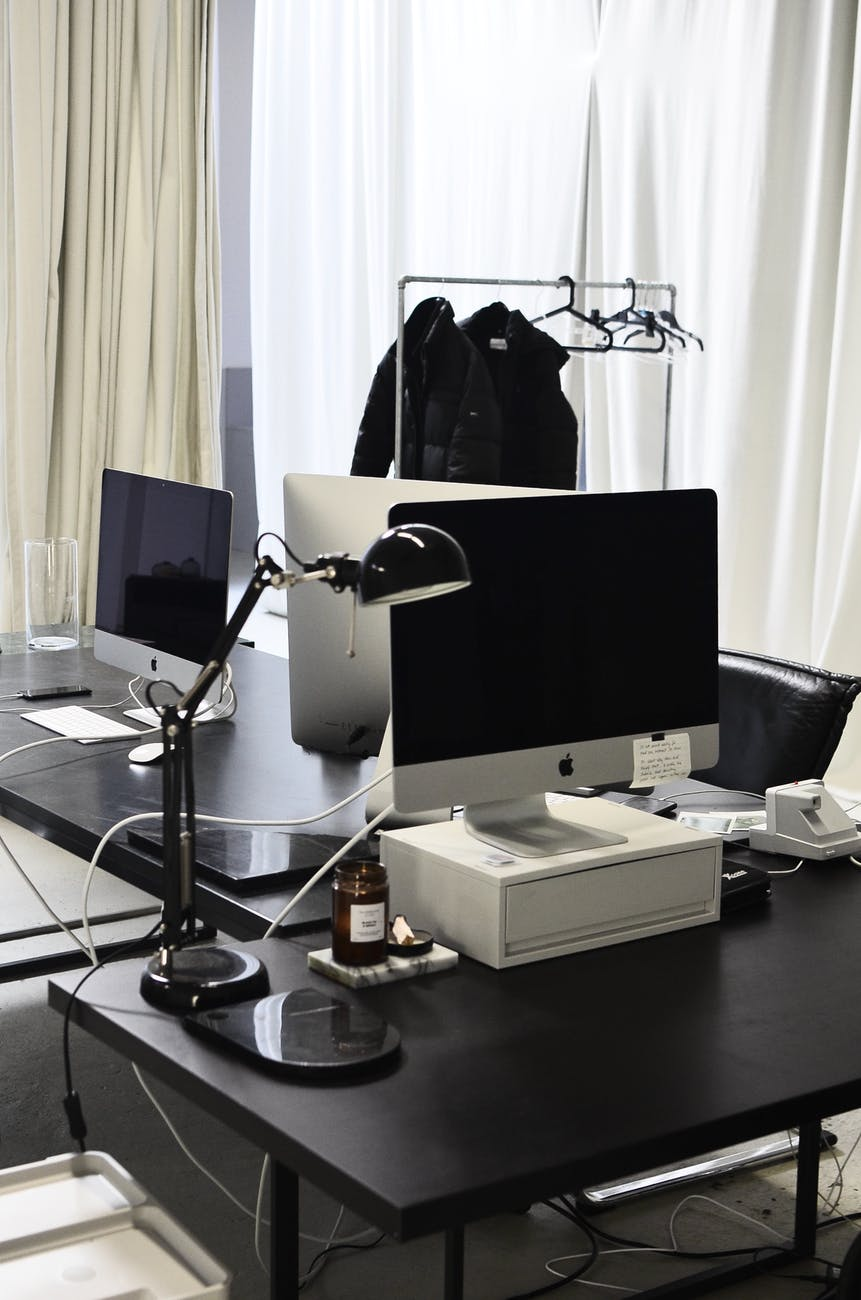 contemporary computers on tables of modern workspace