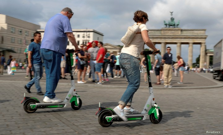 FILE - People use electric scooters by California-based bicycle rental service Lime at the Brandenburg Gate in Berlin, Germany, June 21, 2019.
