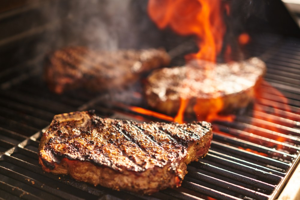 steaks cooking over flaming grill