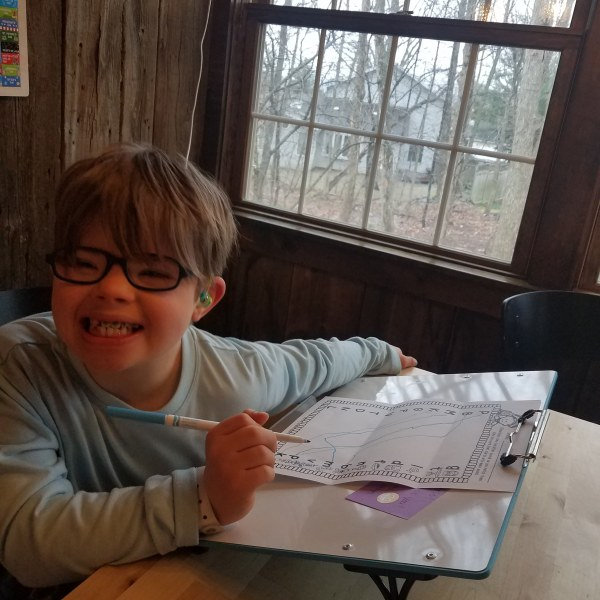 Boy smiling, doing schoolwork at his table.