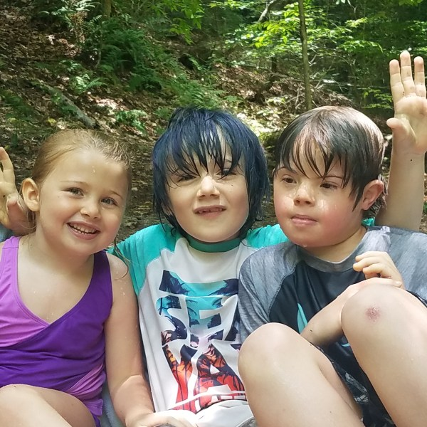 Three children smiling for the camera in a forest