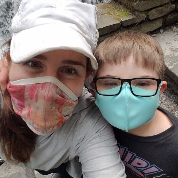 Mother and son smiling under their masks