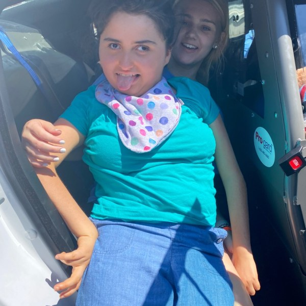 Cailyn in the back of police car during a special day at summer camp.