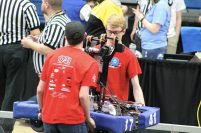 Adam St Louis and Connor Osborne carry the Robot onto the competition field for their match.