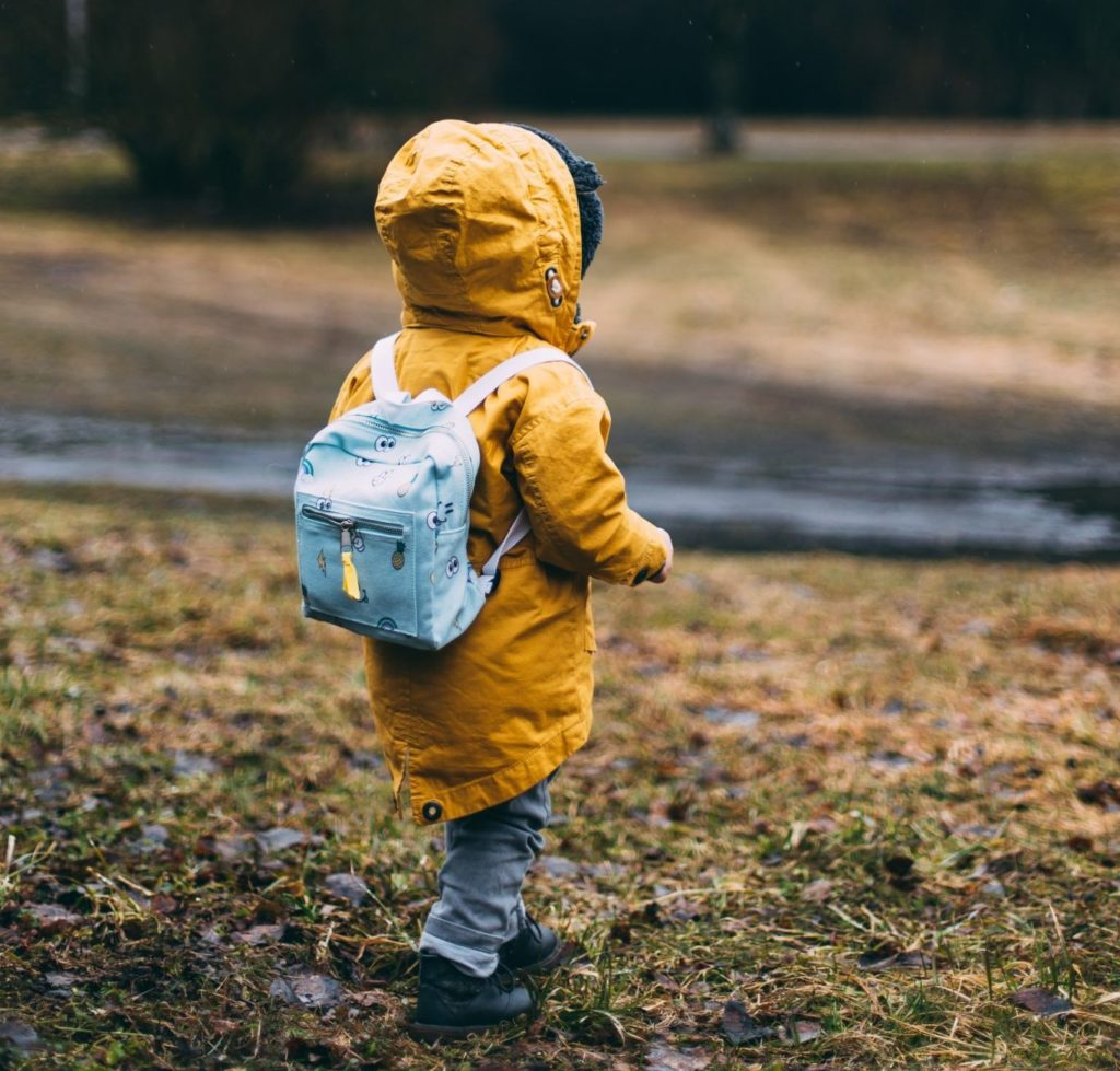 young child in raincoat with backpack