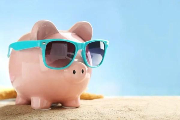 Piggy bank wearing sunglasses on a sandy surface