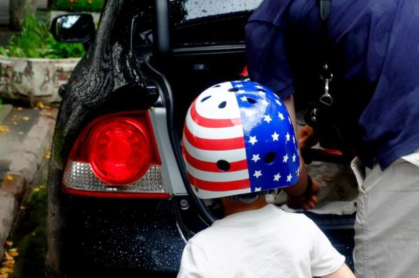 A boy wearing a bicycle helmet painted the USA flag colors