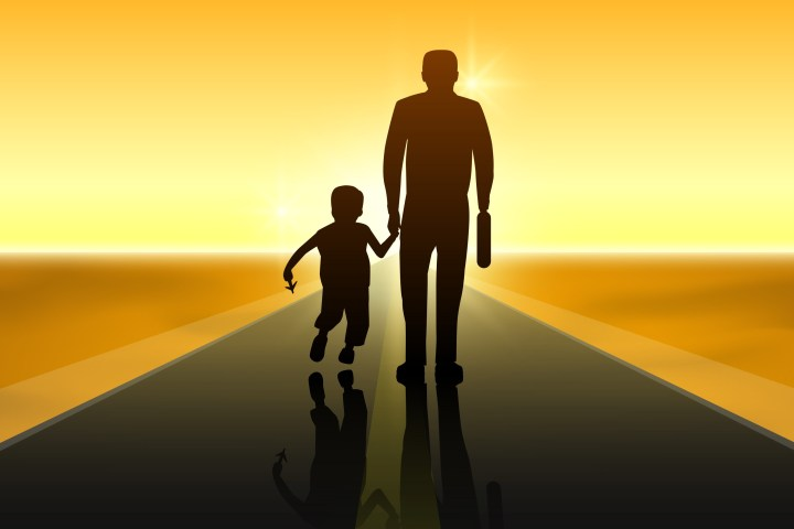 Father and child silhoutted against sunset