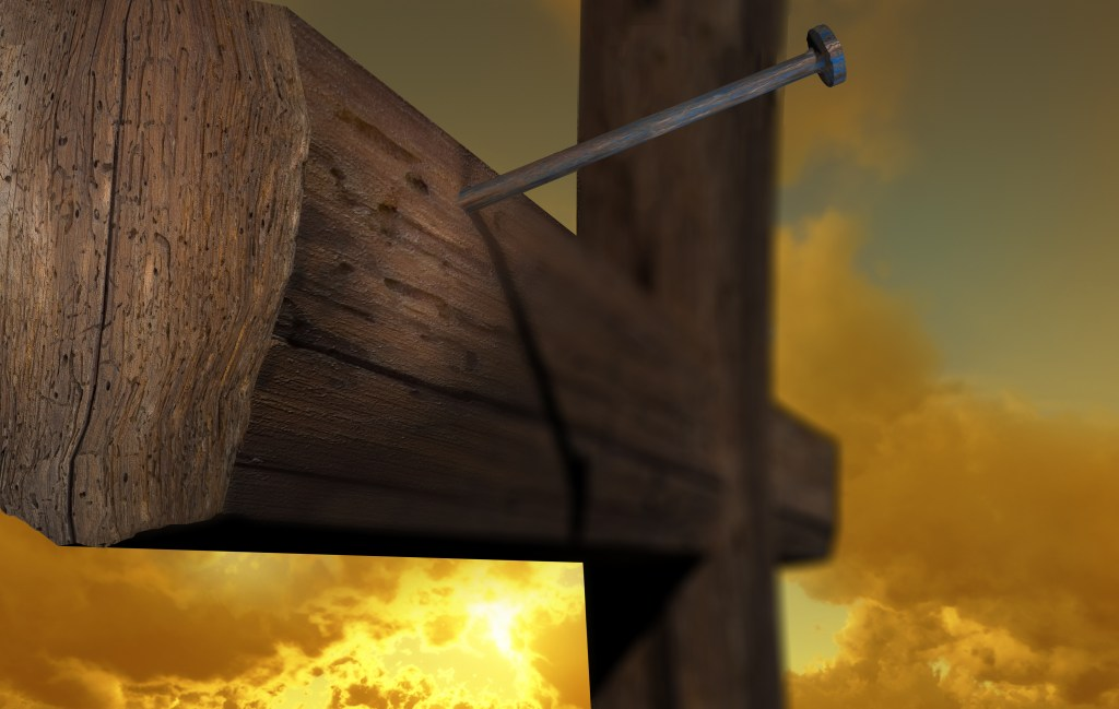 Wooden cross with golden sky in background, one nail in the wood