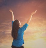 A woman lifts her arms up in praise