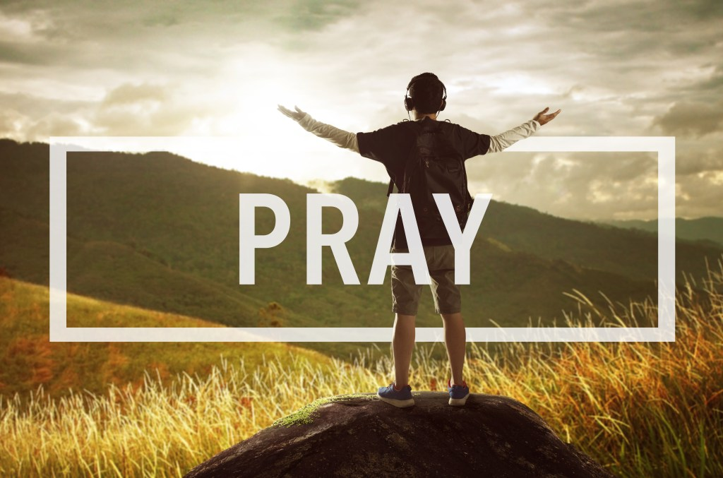 Man standing with arms raised, PRAY superimposed over the image