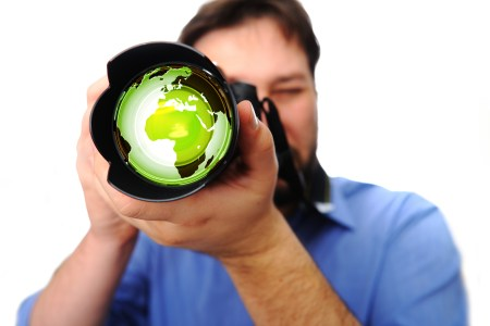 Man holding a camera, image of the world superimposed on the lens.