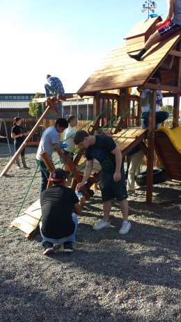 student ambassadors painting weather resistant stain on playground equipment at the Methodist Church.