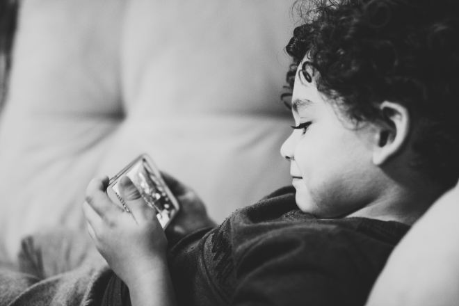child with phone Photo by Diego Passadori on Unsplash