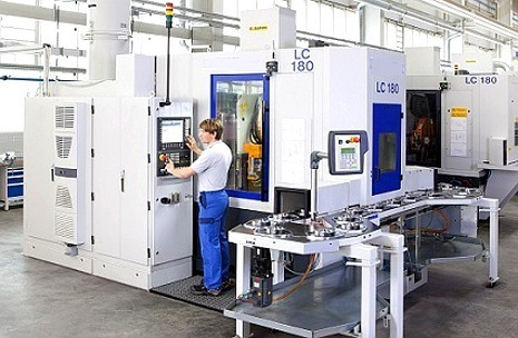 an image of a man standing in front of a large machine shop CNC multi purpose machine used to shape metal