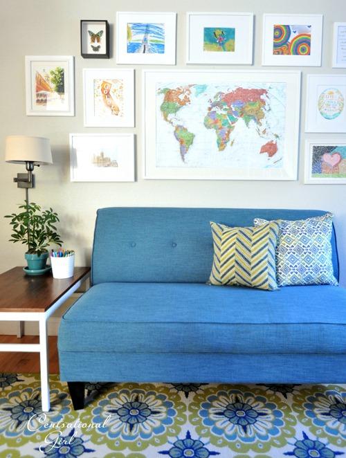 framed world map above blue sofette cg