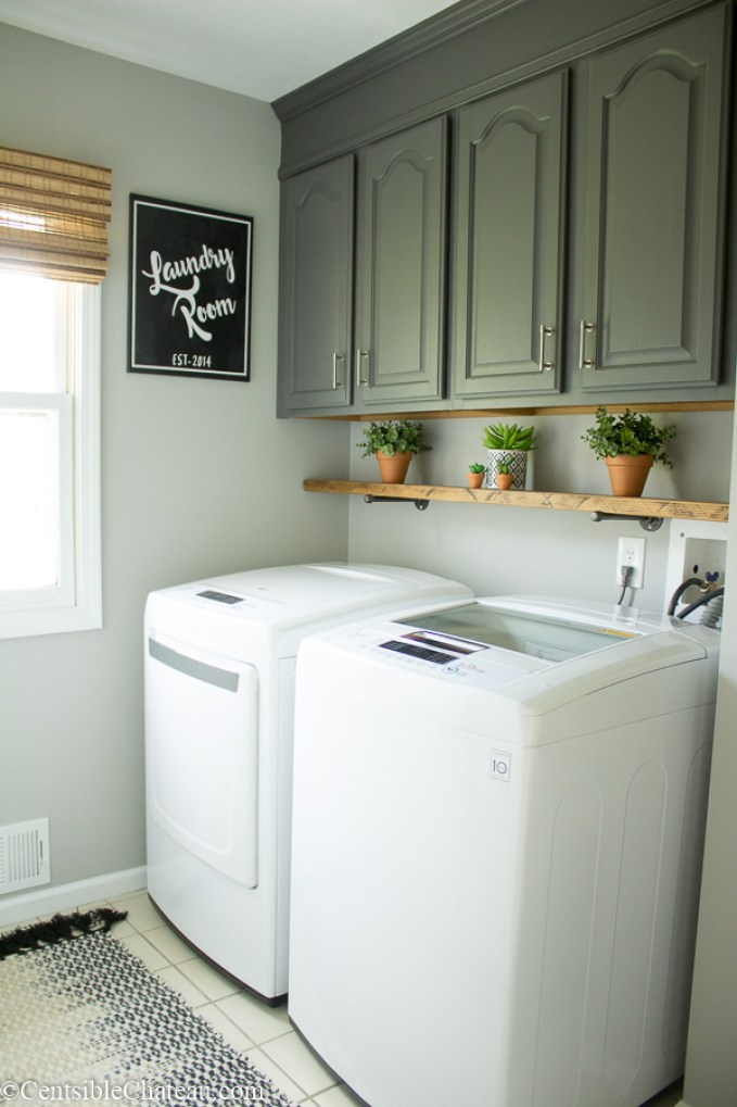 We don't have a massive laundry room or a massive budget, but I really wanted a cute laundry room. See how we created this adorable farmhouse laundry room with freshly painted gray cabinets, a rustic shelf, and some fun accessories! #laundry #laundryroom @centschateau