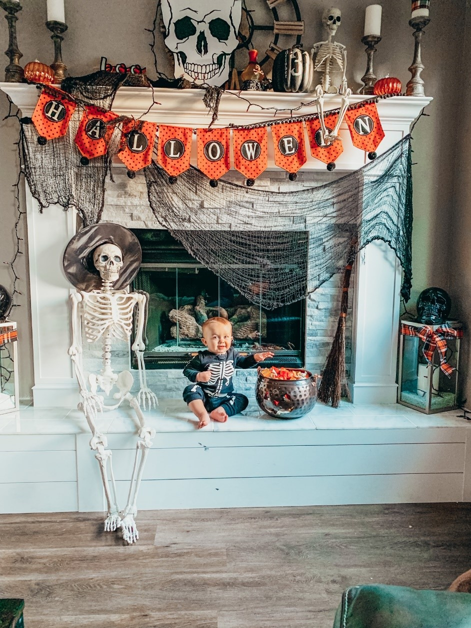 A picture of a Halloween Mantel with Spooky Halloween Decor and a Baby Dressed as a Skeleton trying to grab candy. By A Life We Create