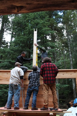 the first post for the ridge beam goes up atop the wall
