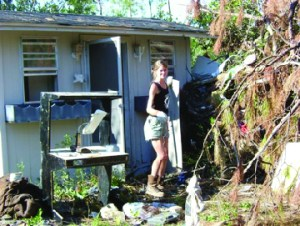 Female artist outside small studio building cleaning up after a hurricane
