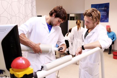 Two men in white working on exercise lab