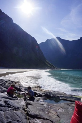 Kids playinga at the beach in Lofoten with mountains in backgraound