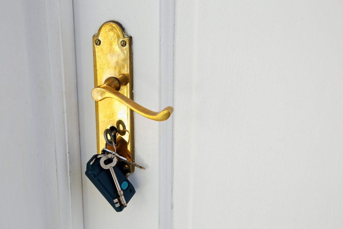 Cómo sacar una llave trabada en la cerradura. Foto de un picaporte con una llave puesta en la cerradura, con otras llaves y un control remoto en el mismo llavero.